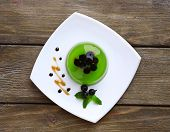 Green jelly with blackcurrant berries and sauce, on wooden background