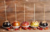 Sweet caramel apples on sticks with berries, on wooden table