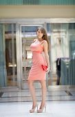 Beautiful young woman in pink dress in the shop