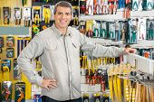 Portrait of happy mature man standing with hand on hip in hardware store