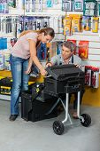 Mature salesman showing tool case to female customer in hardware store