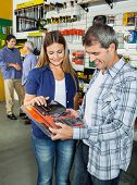 Happy couple buying tool set in hardware store with people hand shaking in background
