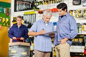 Father and son writing on checklist while worker working in background at hardware store