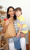 Adorable Little Boy Unpacking Grocery Bag With His Mother