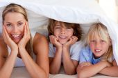 image of mother child  - Attractive mother having fun with her children on bed at home - JPG