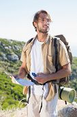 Handsome hiker holding map and compass at mountain summit on a sunny day