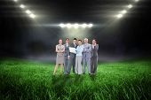 stock photo of football pitch  - Business team looking at camera against football pitch with bright lights - JPG