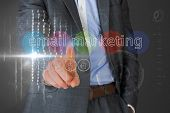 Businessman touching the words email marketing on interface against grey vignette