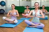 Smiling yoga class in lotus pose in fitness studio at the leisure center