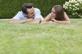 Loving young couple looking at each other while relaxing in park