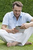Full length of young man using digital tablet in park