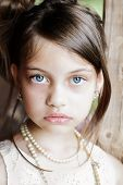 foto of little girls photo-models  - Young girl looking directly into the camera wearing vintage pearl necklace and hair pulled back. Extreme shallow depth of field with selective focus on eyes.