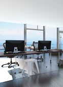 Modern waterfront office overlooking the sea with several computer workstations on movable wheeled office tables in a bright airy room with a glass view window or wall