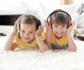 Smiling Siblings Listening Music With Headphones