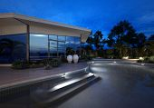Luxury modern villa or house with large plate glass windows at night with an illuminated curving swi