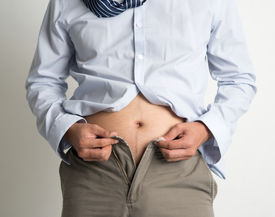 picture of big belly  - Middle age man with big belly unable to close the pants due to gaining weight - JPG