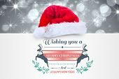 Colourful banner wishing a happy christmas against shimmering light design on grey