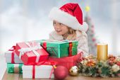 Cute little girl with gifts against blurry christmas tree in room