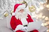 Santa using laptop against christmas decorations on branch