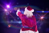 Santa Claus points at something against digitally generated disco design on black