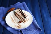 Tasty tiramisu cake on plate, on wooden table