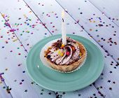 Birthday cup cake with candle with sparkles on plate on color wooden table background