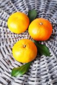 Tangerines with leaves on wicker background