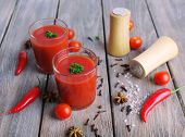 Tomato juice in glasses and fresh vegetables on wooden background