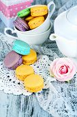 Macaroons on napkin and in cup on wooden table close-up