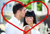Beautiful young romantic couple and heart-shaped frame