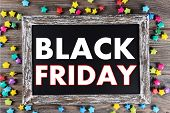 Vintage sign board with Black Friday text on it on wooden background