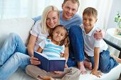 Happy young parents and their children reading book at home