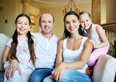 Smiling family of four having rest at home