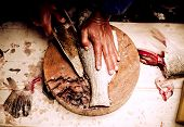 Filleting a large fish cut on the table. close up