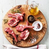 pic of cumin  - Raw fresh lamb ribs with salt pepper and cumin on wooden cutting board on blue background - JPG