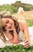 Romantic girl with flower in the hand lying down outdoors