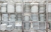 picture of racks  - Stacks of many white plates on a wire rack shelf in a commercial kitchen - JPG
