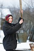 woman with  bucket collecting water from  well