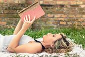 Romantic girl reading a book lying outdoors