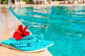 Turquoise Flip Flops And Flower On The Edge Of The Pool