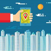 Smartphone with map & location in human hand on the background of the city for presentation and diff