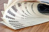 picture of yen  - Japanese Yen Cash Bank Note on wooden table - JPG