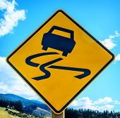 stock photo of slippery-roads  - Yellow slippery road sign with blue sky background