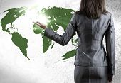 Rear view of businesswoman pointing at world map