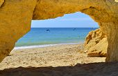 Natural stone arch on Armacao De Pera Beach with dolphins swimming