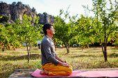 man meditates in garden