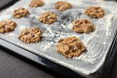 stock photo of baked raisin cookies  - uncooked oatmeal cookies with raisins on baking tray - JPG