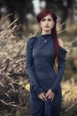Red-haired Girl In A Long Blue Dress In The Forest
