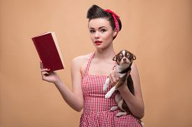 picture of pale skin  - Portrait of pretty brunette  girl in rose dress and red headband in retro style  with Chihuahua reading book  looking at camera  waist up - JPG