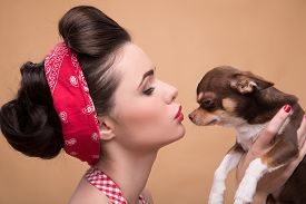 stock photo of pale skin  - Portrait of pretty brunette  girl in rose dress and red headband   in retro style  kissing  cute Chihuahua puppy on beige background close up - JPG